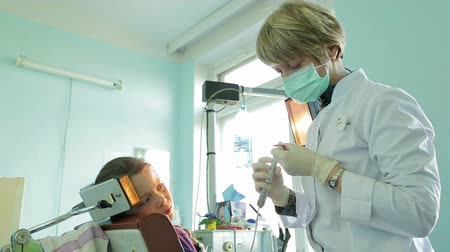 dentysta : Girl watching orthodontist correcting braces for crooked teeth with dental instrument.