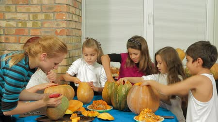 groupe : Two adults and four little children are carving Halloween pumpkins.