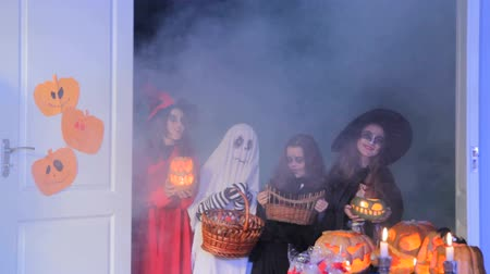groupe : Children sing a trick-or-treat song and a woman gives them sweets.