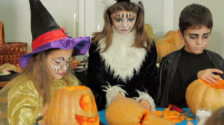 groupe : Three children in a costumes and with make-up for Halloween are carving pumpkins.