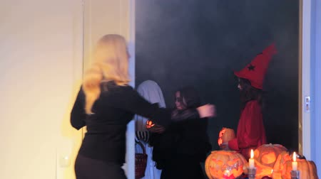 groupe : Woman ways good-bye to children in costumes who sang a trick-or-treat song and closes the door. Stock Footage