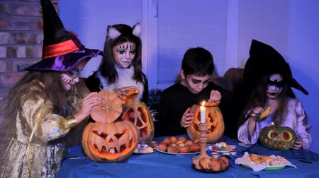 groupe : Children in a costumes and with make-up for Halloween lighting candles in a magic way. Stock Footage