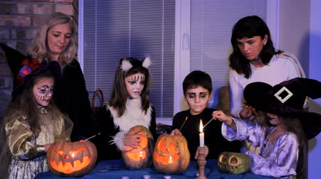 groupe : Two adults and four children in costumes in scary make-up light candles inside Halloween pumpkins. Stock Footage