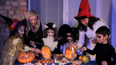 groupe : Four children in Halloween costumes in scary make-up and two adults light candles which are on the table.