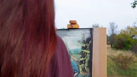 kahverengi : Rear over shoulder view of a woman with long brown hair in warm clothes making a sketch of a landscape around her on the easel. Crane shot moving over the painter up to the beautiful autumn landscape with footpath.