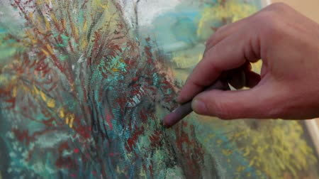 ručně malovaná : Extreme close-up footage: hand of a woman painter drawing a picture of an autumn landscape on the easel with a help of multi colored chalks, adding lines. Dostupné videozáznamy