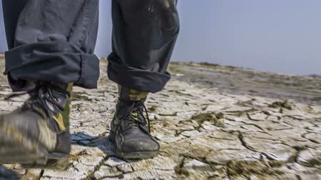 száraz : Low angle footage, camera following the legs of a researcher at the valley who is walking on the split soil. Footage in RAW format near Kerch, Crimea. Stock mozgókép