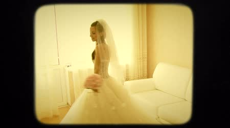 nevěsta : Young beautiful bride in white wedding dress and veil is spinning around in white room with a bouquet in her hands. The window with curtains and sofa are behind her. Video shot in retro style.