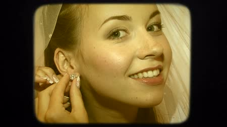 brincos : Two frames: portrait of a beautiful young cheerful black-haired bride putting a silver brilliant earing -stud on her earlobe with a happy facial expression. Second frame - super close-up focused on the ear, earing and hands of the bride. Stock Footage