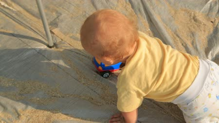 crawlers : Video footage of a small baby boy in yellow babys jacket and colorful crawlers holding and rolling a car toy in his hands crawling on cloth with sand being a mat on the beach. Shot from above. Camera is following a baby.