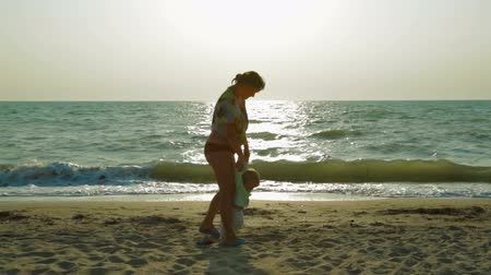 krím : Happy mother playing with her baby boy at sandy beach - first they are walking together holding hands, after  mother throwing baby up and embracing then they leave. Shot is made in Crimea at the Black sea with small waves. The sun is reflected on water.