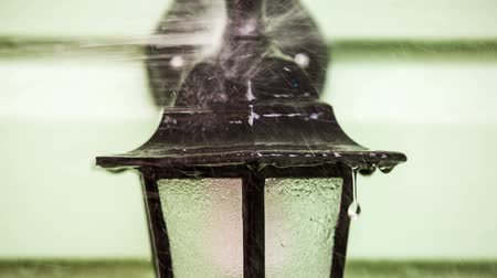 pulverizado : CLOSE UP: In the frame there is a shot of a human washing and spraying a special detergent in the form of antibacterial foam onto the decorative street lamp of a house hanging on blurred light green wall while the process of general cleaning. Stock Footage