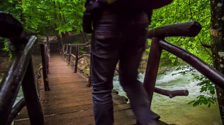 подвесной : In the frame there is a back shot of a tourist with backpack walking along wooden bridge hanging above rough river with stones and swinging at each step.