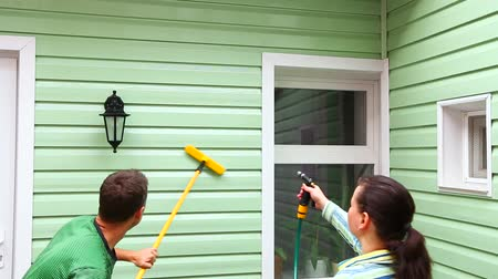 cleaning equipment : This is a shot of a light green wall of a house with a window and a man cleaning it with long brush and a woman washing it with help of hose from up during general cleaning.