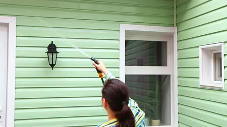 sprzataczka : This is a shot of a light green wall of a house with a window and a woman washing it with help of hose from up and a man cleaning it with long brush during general cleaning. Wideo