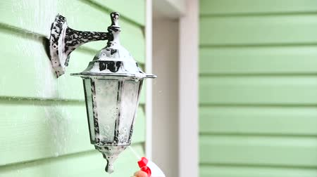 pulverizado : CLOSE UP: In the frame there is a shot of a human hand spraying a special detergent in the form of antibacterial foam onto the decorative street lamp of a house hanging on blurred light green wall while the process of general cleaning. Stock Footage