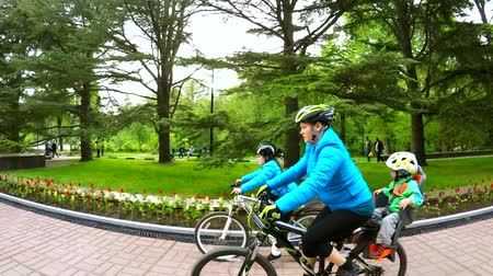 cyclists : SLOW MOTION: Side shot of a young mother with little son on backseat and daughter in helmets and blue jackets riding bicycles along asphalt road in green park. Stock Footage