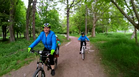 cyclists : SLOW MOTION: This is a shot of a happy mother with her little son sitting on backseat and daughter riding bikes along footpath wearing protective helmets and blue jackets in green park and smiling.