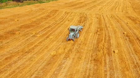 hay pile : This is an aerial shot over golden stubble field with a light blue farm tractor baler slowly driving across it. There are some bales lying around. Hilly terrain with greenery and cloudscape of background.
