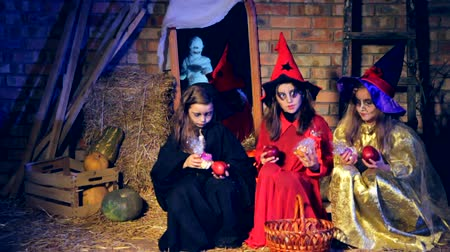 trik : Group of three little girls in costumes of witches sitting and playing with apples and after a while see a ghost in white cloth and run away with cries. Dostupné videozáznamy