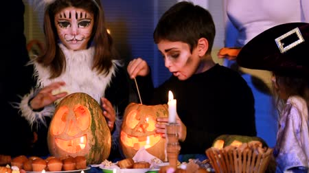 dynia : This is a portrait of a little boy standing next to the girls in holiday costumes and lighting Halloween candle inside carved pumpkin with help of long match. Wideo