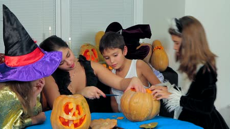 zanaat : Group of children in Halloween costumes watching a young woman sitting at the table and carving a pumpkin preparing for the holiday celebration party. Stok Video