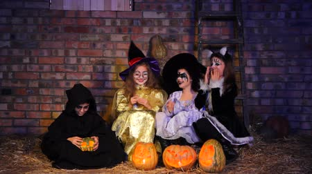 kostüm : In the frame there is a little monster in black clothing doing magic with a pumpkin creating smoke. Three little Halloween witches get scared and run away.