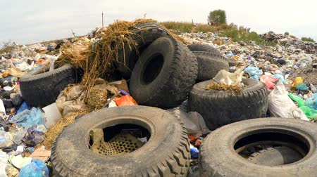 yards : In the frame there is a moving shot over lots of garbage, wastes, trash and litter with used car wheels and rubber dumped into a huge heap and packages swaying on the wind. Natural disaster. Stock Footage