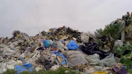 езда с недозволенной скоростью : CLOSE UP: This is a video shot over large pile of ejected domestic wastes and garbage dumped at grass with cloudy sky on background, environmental problems in Ukraine.