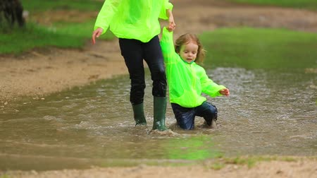 fall down : Happy Girl And Boy Having Fun In Huge Puddle Stock Footage