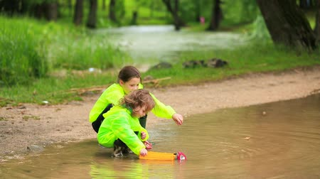 small park : Cute Kids Playing Cars In Huge Puddle In Park