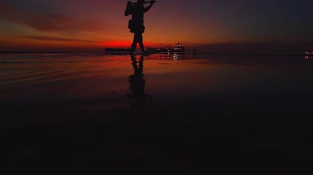 industrial fishing : Silhouette. A man crosses the beach with a view of the sunset on the beach