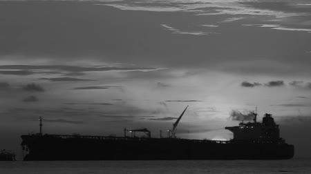 тон : Black and white tone. Beach with views sunset of the background of a cargo ship anchored at dusk Стоковые видеозаписи