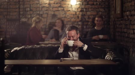 caffe : happy businessman with phone in a cafe drinking coffee