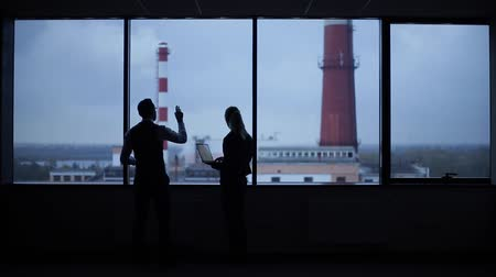 belirtmek : Silhouettes of busy workers standing against the window