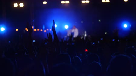 eufória : Excited people waving hands up in air, enjoying music at concert