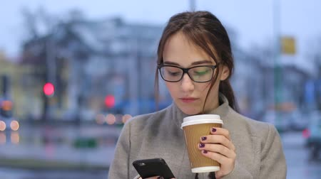 Young female uses her smartphone while drinking coffee outdoors.