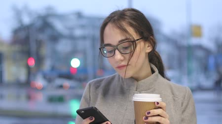 Young female drinking coffee and browsing in her smartphone outdoors.