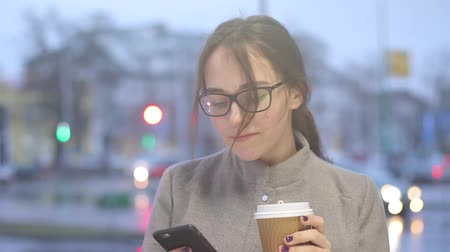 Pretty young girl checks social media on her phone while drinking coffee.