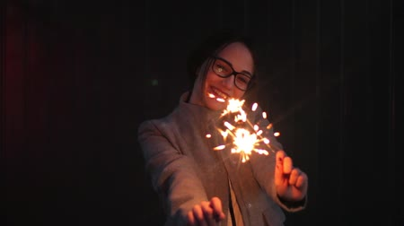 Portrait of a happy teenage holding sparklers in her hands. Dostupné videozáznamy