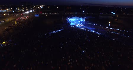 Huge concert from the air. Lots of people jumping, waving hands, clapping