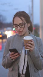 Pretty young female standing on the street drinking coffee and cheking social media on her phone.