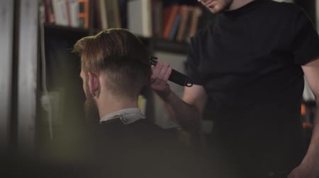 Barber cuts the hair of the client with trimmer