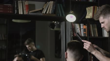 Stylish male barber blow-dries clients hair