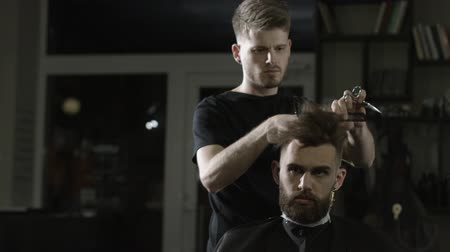 Shot of professional hairdresser cutting male hair with scissors.