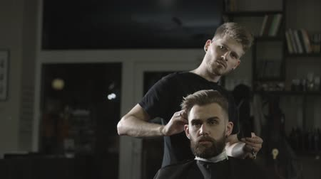 Young professional barber making haircut of attractive bearded man in barbershop
