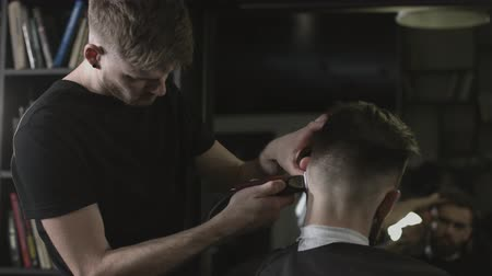 Haidresser makes a male haircut with a hair trimmer in a fashionable barbershop