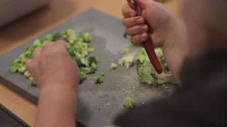 Womans hands cutting brocoli with knife.