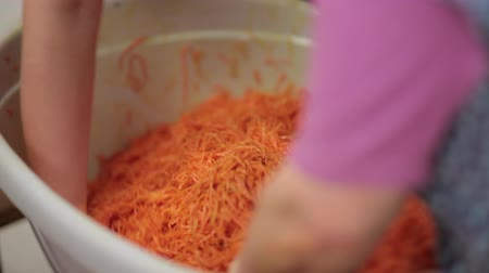 Women mixing carrot salad. Korean carrot close up