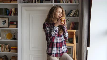 Beautiful young woman drinking coffee by the window Dostupné videozáznamy